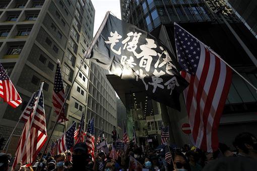 美國新聞網站Axios 1日刊登一篇文章,內容提到因美國通過「香港人權與民主法案」,激怒中國,美中貿易協議談判中斷。圖為香港民眾1日遊行揮舞「光復香港」旗幟及美國國旗。(美聯社)