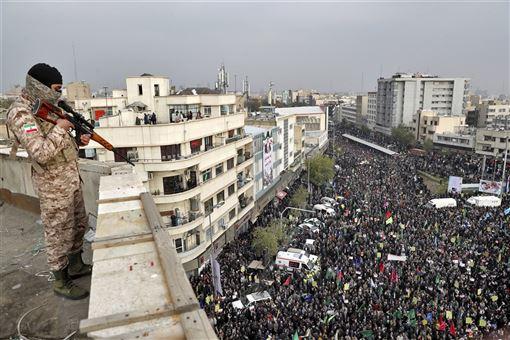伊朗正經歷40年前伊斯蘭革命以來最血腥的政治動亂,憤怒的示威群眾如今正籠罩政府放任武力鎮壓的陰影。圖為25日軍隊持槍俯視集會民眾。(美聯社)