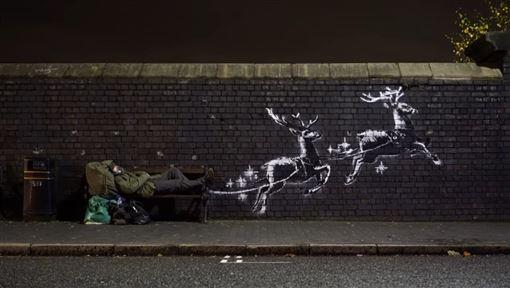英國知名塗鴉藝術家班克西又有耶誕新作品,他在一張遊民棲身的長椅旁,畫上兩頭替耶誕老人駕車的馴鹿。(圖/翻攝自banksyfilm YouTube頻道網頁youtube.com)