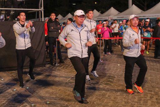 柯文哲出席台北馬拉松(3)2019台北馬拉松15日在台北市政府前廣場開跑,台北市長柯文哲(前中)、田徑好手楊俊瀚(後排左)、陳傑(後排右)出席與會,在賽前與跑者一起做操熱身。中央社記者裴禛攝 108年12月15日