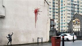 英國知名塗鴉藝術家班克西(Banksy)據信送給家鄉布里斯托一份情人節禮物,那就是出現在牆上的新作品,畫中可見一名小女孩手持彈弓射出一簇紅花煙火,居民發現後都相當驚喜。(圖/取自班克西IG網頁instagram.com/banksy)