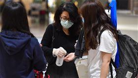 家長機場接小孩 手部先消毒受到武漢肺炎疫情影響,桃園國際機場22日清晨出現不少旅客返台,不少家長和孩子碰面後,先幫孩子進行消毒。中央社記者林俊耀攝  109年3月22日