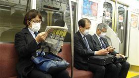 武漢肺炎疫情擴散,東京民眾憂封城,搭乘地鐵民眾閱讀頭版為「封城進入秒讀」的報紙。中央社記者楊明珠東京攝 109年3月26日