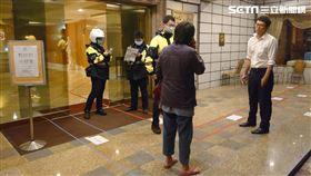 北投分局光明所警員及里長陳惠華在防疫旅館門口止步。(圖/里長提供)