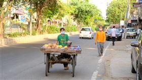 新德里兒童沿路兜售水果印度政府執行全國封鎖,仍允許販售蔬果食品攤販推車外出營業,以免更多窮人失業無法維持生計。圖為少年推車沿路兜售水果。中央社記者康世人新德里攝  109年5月6日