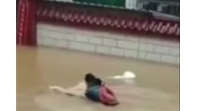 一段名為「爸爸游泳背女兒高考」的影片在網路上瘋傳。(圖/翻攝自搜狐)