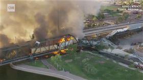美國亞利桑那州29日清晨發生火車出軌事故,一列貨運列車在坦佩鎮湖橋樑上出軌,列車全面燃燒引發巨大火勢與濃煙,現場近百位消防員投入控制火勢。(圖取自CNN網頁cnn.com)