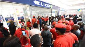 南非知名藥粧連鎖超市克里克斯,上週在網頁刊出一則歧視黑人女性頭髮的美髮品廣告,引發眾怒。第三大政黨經濟自由鬥士於7日號召黨員到克里克斯各地分店示威。(圖/翻攝自facebook.com/economicfreedomstruggle)