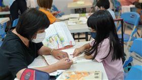 課輔班志工指導孩童。(圖/呂凱庭提供)