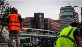 針對在「反送中」示威衝突中有人冒充記者在前線採訪,香港警方決定修訂媒體代表定義。圖為2019年11月19日警方包圍香港理工大學,並在校區外設防線,大批媒體校外守候消息。(中央社檔案照片)